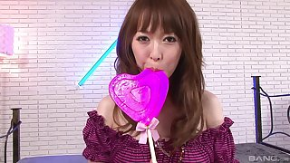Japanese teen fetish model plays with a lollipop and her tits